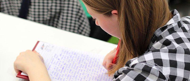 Photo jeune fille écrivant sur un bloc